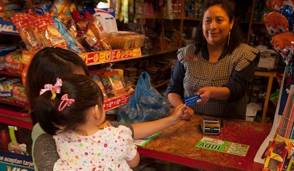woman holding a child handing over visa credit card to woman cashier in store